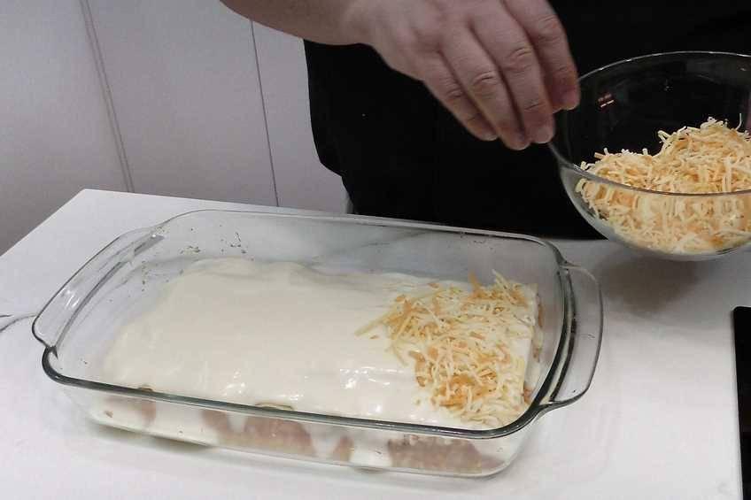 Volcar la bechamel y poner el queso rallado