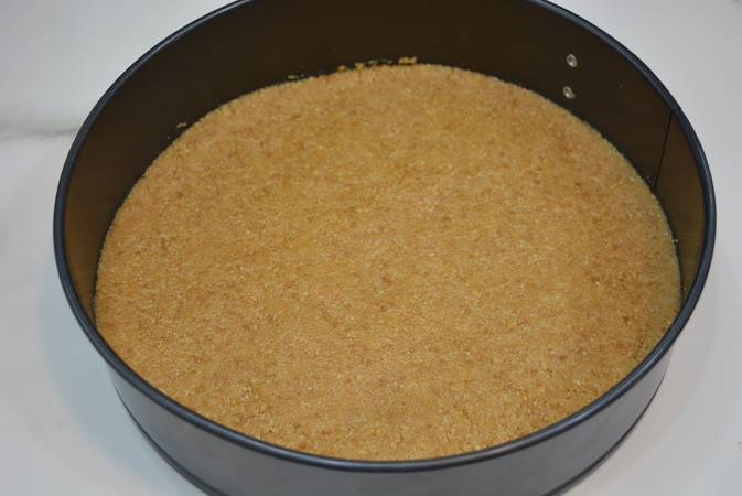 Mezclar la galleta con la mantequilla y poner la base en el molde