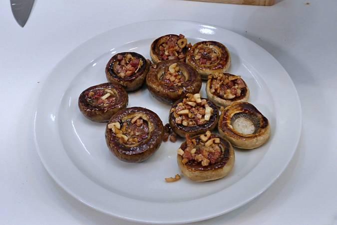 Poner el refrito de ajo y jamón en los champiñones
