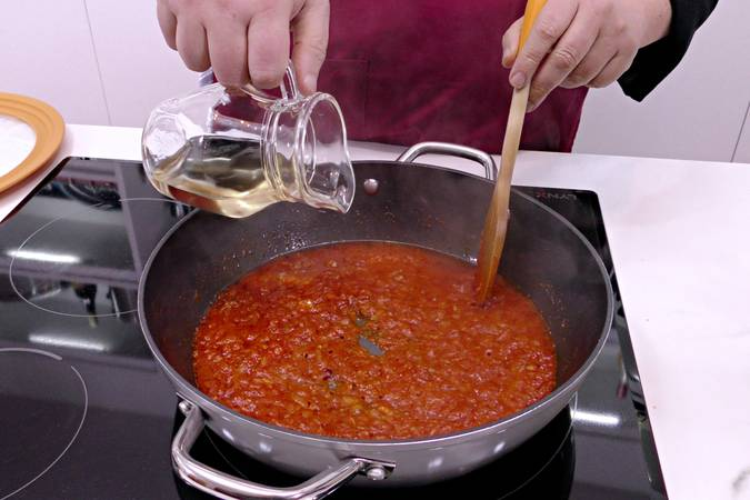 Añadir el tomate frito y el vino blanco