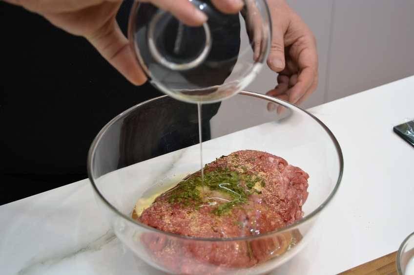Ponerle los aderezos a la carne para hamburguesas